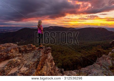 Storm Clouds Hover Over Blue Mountains And Valleys As The Sun Sets.  A Woman Stands On The Rocky Pre