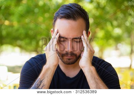Stressed Young Man Rubbing Temples. Young Bearded Man With Closed Eyes Suffering From Headache Outdo