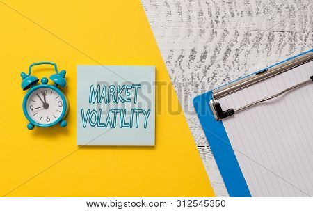 Conceptual hand writing showing Market Volatility. Business photo showcasing Underlying securities prices fluctuates Stability status Notepad colored paper sheet alarm clock wooden background. poster