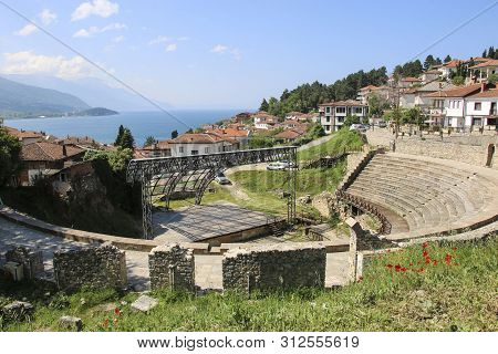 Antique ancient roman amphitheater or antique theatre of Ohrid with view on old town of Ohrid and Lake Ohrid, Republic of North Macedonia poster