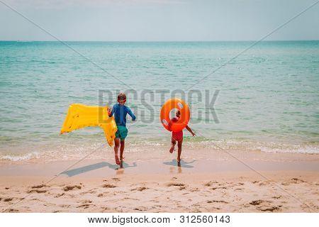 Happy Boy And Girl With Floaties Run Swim On Beach