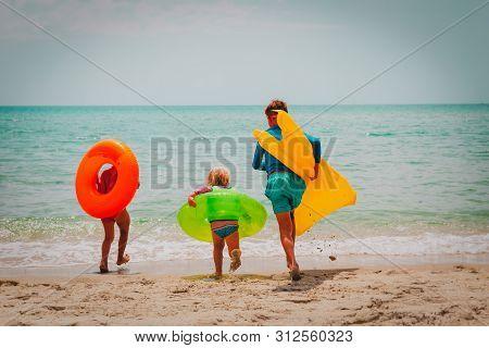 Happy Boy And Girls With Floaties Run Swim On Beach