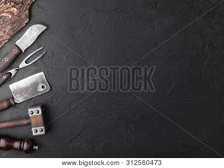 Vintage Meat Knife And Fork And Hatchets With Vintage Chopping Board And Black Table Background. But