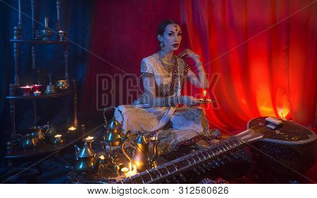 Beautiful Young Indian Woman In Traditional Sari Clothing And Oriental Jewelry With Candle, And The