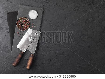 Vintage Meat Knife Hatchets With Stone Chopping Board And Black Table Background. Butcher Utensils.