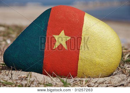 cameroun flag colours on a stone on the beach