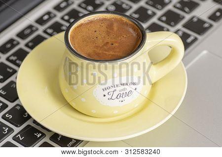 Turkish Coffee Inside Yellow Cup On Keyboard Laptop At Morning