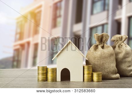 Property Investment Concept. A Small House Model With Stack Of Coins And Money Bag On Table. Depicts