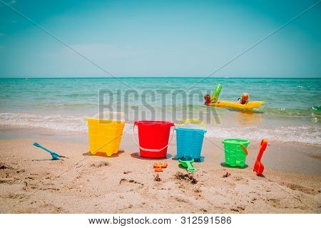 Toys And Kids Play On Beach Vacation, Family At Sea
