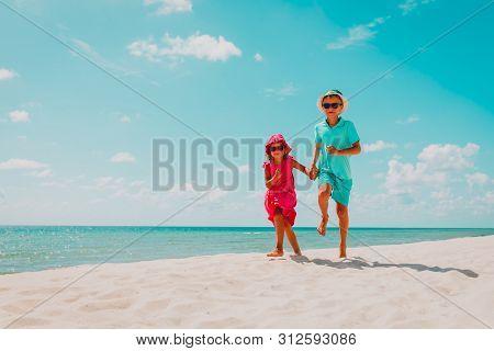 Happy Cute Boy And Girl Running On Beach