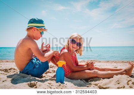 Sun Protection, Cute Girl And Boy With Sun Cream At Beach