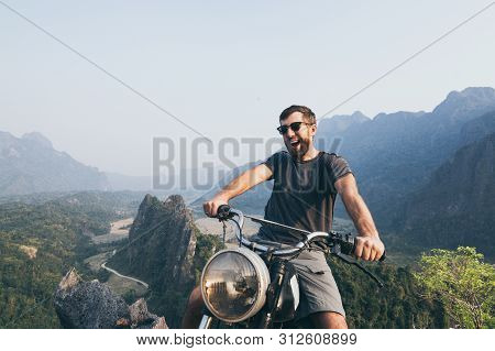Caucasian Young Man Riding Vintage Motorcycle On Top Of The Mountains In Vang Vieng, Laos.