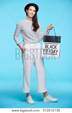 Young female shopper in smart casual boasting with black friday purchase