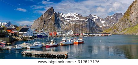 Hamnoy Village on the Lofoten Islands, Reinefjord,  Norway. Panoramic Shot,  Fishing boats in harbor on Lofoten Islands,  Norway - Mountain In Background