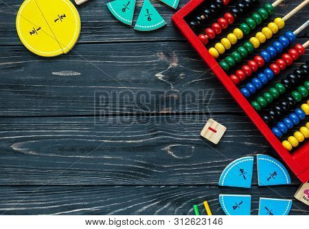 Creative Сolorful math fractions on dark background. Interesting funny math for kids. Education, back to school concept. Geometry and mathematics materials. Flat lay, top view poster