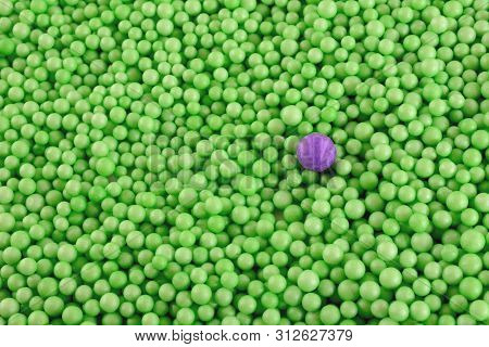 One Purple Polystyrene Ball In A Crowd Of Green Smaller Polystyrene Balls As Visual Concept Of Diffe
