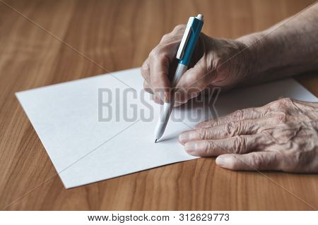 Old Woman Pensioner Writes On A Piece Of Paper. Pensioner Writes In Pen On Paper.