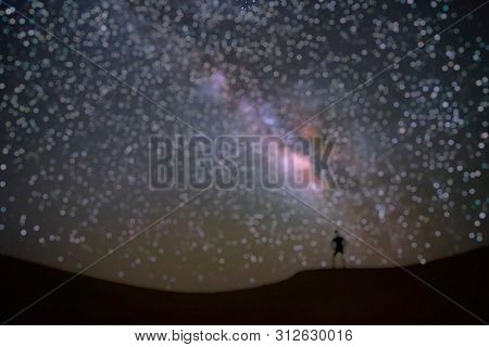 Out Of Focus Of Milky Way Galaxy With A Man Standing And Watching At Tar Desert, Jaisalmer, India. A