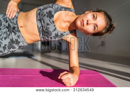 Home fitness yoga training Asian girl working out side planking bodyweight exercises on exercise mat in apartment condo. Woman planking doing core body for fit obliques muscles.