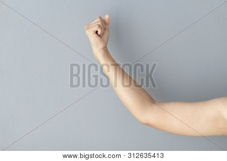 Woman Hand With Clenched Fist On Grey Background, Health Care And Medical Concept