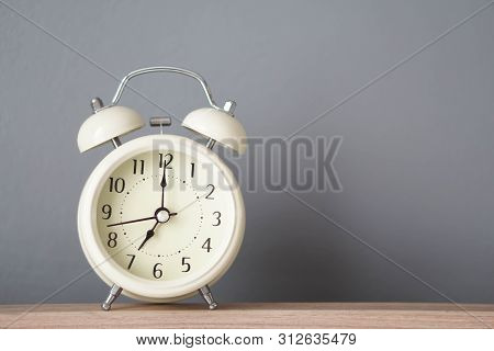 Alarm Clock On Wooden Table With Grey Background, Selective