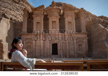 Asian Woman Tourist In White Dress Sitting And Looking At Ad Deir Or El Deir, The Monument Carved Ou