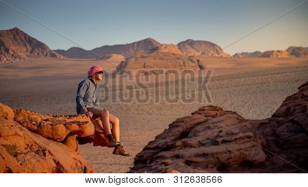 Young Asian Man Traveler Sitting On The Rock In Wadi Rum Desert Looking At Sunset, Famous Place In J