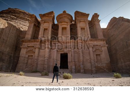 Young Asian Man Traveler And Photographer Holding Camera Standing At Ad Deir Or El Deir, The Monumen