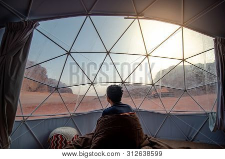 Tourist Man Staying In Blanket In Dome Tent Looking Outside At Wadi Rum Desert, Famous Natural Attra