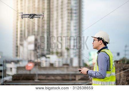 Asian Engineer Man Flying Drone Over Construction Site. Male Worker Using Unmanned Aerial Vehicle (u
