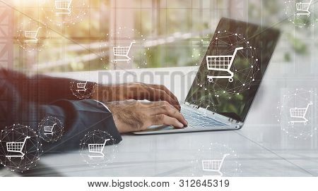 Shopping Icons With Businessman And Laptops In Background. Online Shopping Or E-commerce Concept.