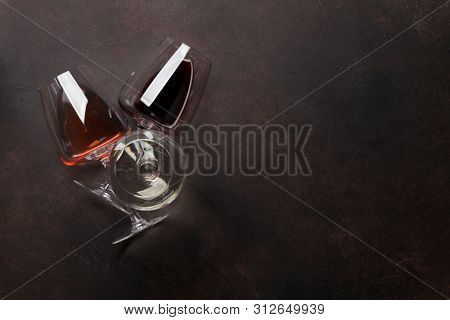 Various wine glasses on stone table. Red, rose and white wines. Top view flat lay with copy space for your text