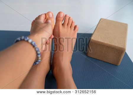 Yoga stretches big toe pull stretch exercises woman doing hamstring stretching at home on fitness mat training stretching legs touching toes. Hand wearing mala bracelet with yoga block. poster