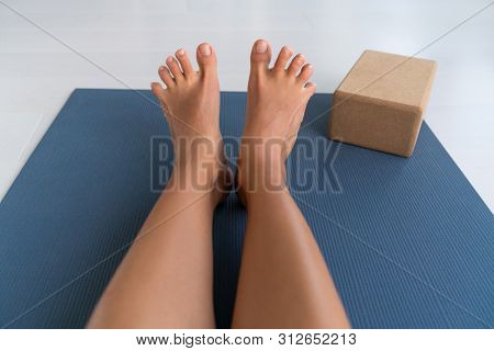Yoga woman stretching feet spreading her toes doing toe stretch on exercise mat of living room floor at home. Foot exercises stretches fun.