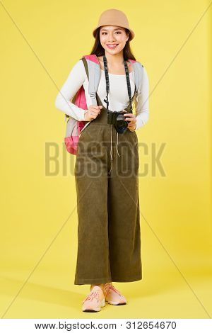 Cheerful Young Vietnamese Woman With Backpack And Digital Camera Smilng At Camera, Isolated On Yello