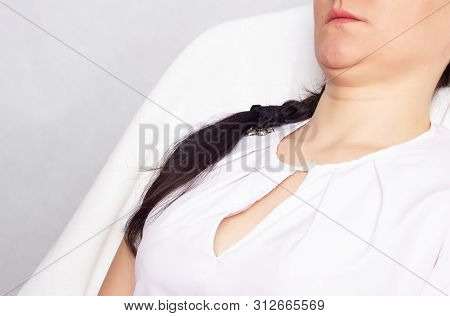 A Girl With A Double Chin Is Sitting On A Chair. Cosmetology, Problem, Copy Space, Dewlap