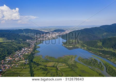 Piatra Neamt City And Lake  On Green Mountain Valley Of Bistrita River In Romanian Carpathians.