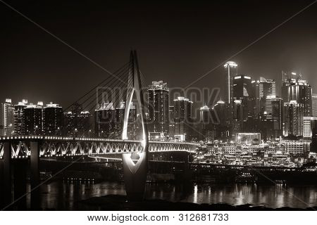 Qiansimen Bridge with Hongyadong shopping complex and city urban architecture at night in Chongqing, China.
