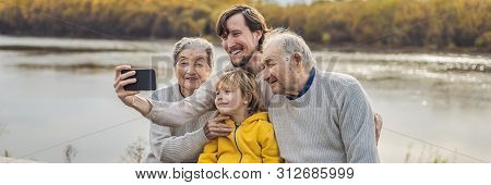 Banner, Long Format Senior Couple With With Grandson And Great-grandson Take A Selfie In The Autumn