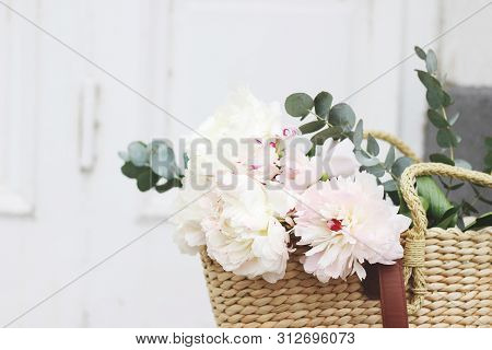 Feminine Wedding Still Life Composition. Straw French Basket Bag With Pink Peonies Flowers And Eucal