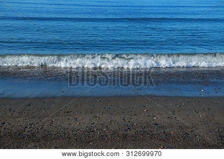 Pristine Blue Water, Dark Sand And Mild Surf Of The Bering Sea In Nome Alaska.