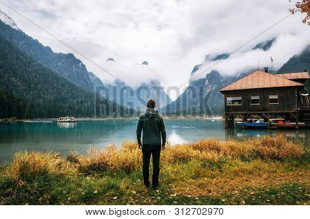 Young Man Hiker Stands Back To Camera On Shore Of Dobbiaco Lake Or Toblacher In Dolomites With Woode