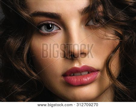 Closeup face of a beautiful woman with a smoky eye makeup. Sexy and gorgeous brown-haired woman with long curly hair. Portrait of an attractive female posing at studio. Hair cover eye.