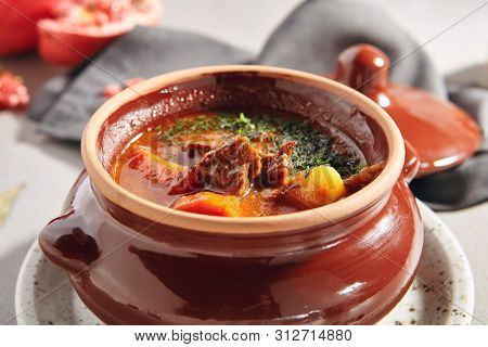 Traditional tasty hungarian goulash soup of beef meat and vegetables close up. Delicious meat stew or red casserole with tomato, potato, greens and chili in ceramic cookware