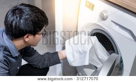 Asian Man Loading White Clothes Into Front Door Washing Machine In Laundry Room. Housework Or Chores