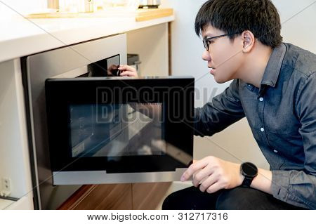 Asian Man Opening Microwave Door In The Kitchen Showroom. Buying Cooking Appliance For Domestic Kitc