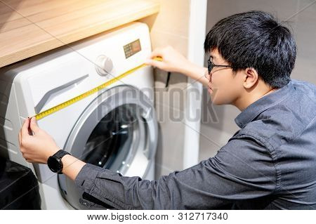 Asian Technician Man Using Tape Measure For Measuring Washing Machine Under Wooden Counter. Applianc