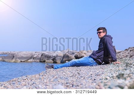 Guy On Spring Vacation Travel. Man Tourist Traveller Comes To Stone Beach Sits And Looks At Sea. He