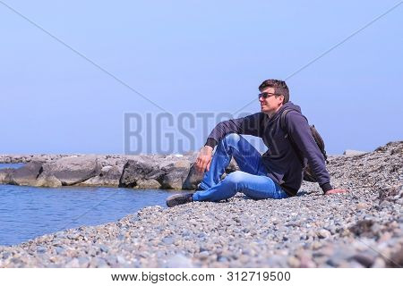 Guy On Spring Vacation. Happy Man Tourist Traveller Sits At Stone Beach And Looks At Sea On Vacation