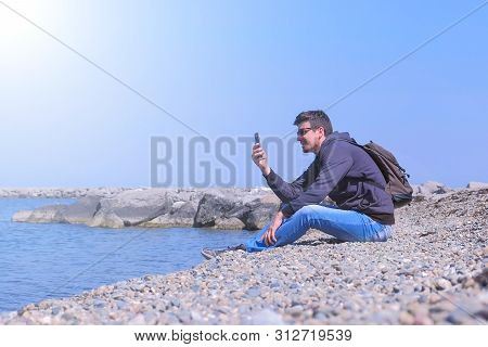 Man Talks Video Chat In His Smartphone Sits On Sea Stone Beach On Vacation. Guy On His Spring Vacati